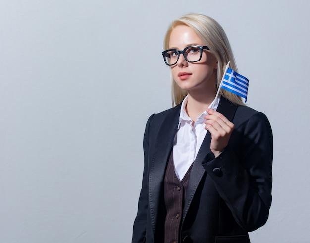 Schöne blonde geschäftsfrau im anzug mit griechenland-flagge auf grauem hintergrund