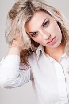 Schöne blonde geschäftsfrau im weißen hemd