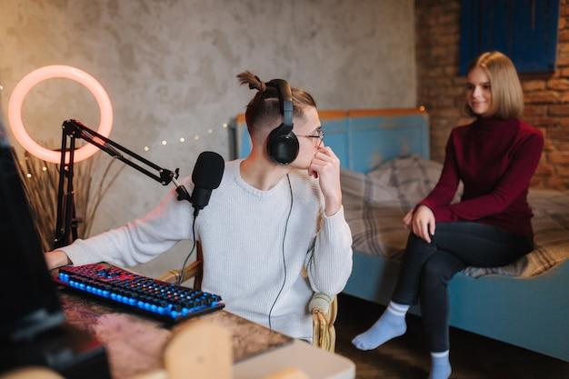Schöne blonde haar freundin sitzt auf dem bett und lokking auf ihrem freund, der am computermann arbeitet