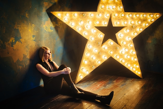 Schöne blonde junge frau, die auf dem boden auf dem hintergrund eines sterns mit lampen sitzt.