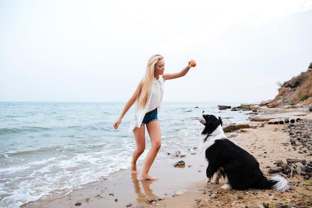 Schöne blonde junge frau, die mit hund am strand spielt