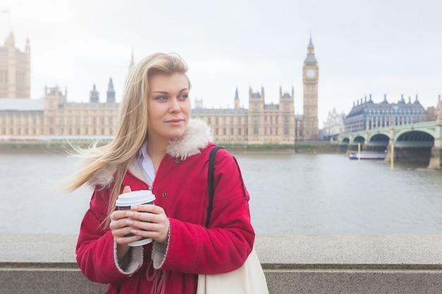 Schöne blonde junge frau, die tasse tee in london hält