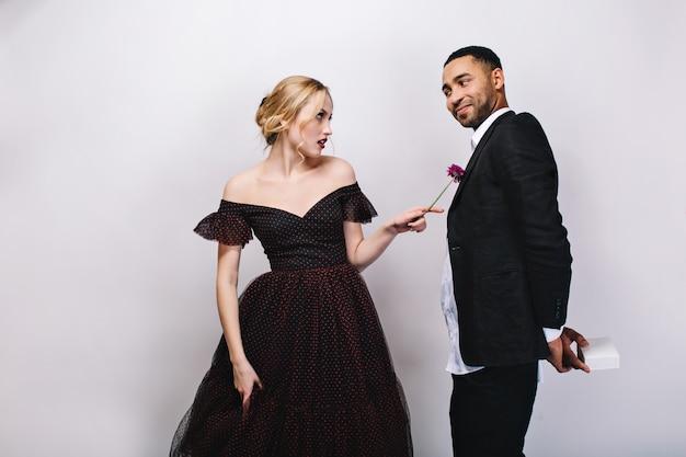 Schöne blonde junge frau im luxusabendkleid, das unzufrieden auf gutaussehenden freund im smoking schaut. lustige momente des schönen paares, überraschung, valentinstag.