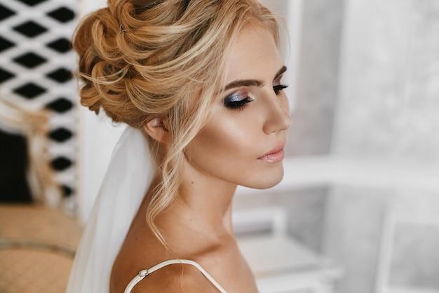 Schöne blonde junge frau mit perfektem make-up und mit stilvoller hochzeitsfrisur in modischen weißen spitzenwäsche, die am weinleseinnenraum aufwirft