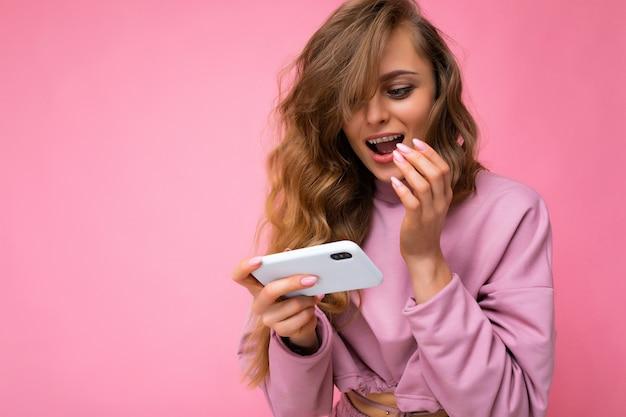 Schöne blonde junge frau mit rosa hoodie isoliert über rosa hintergrund mit kopierraum