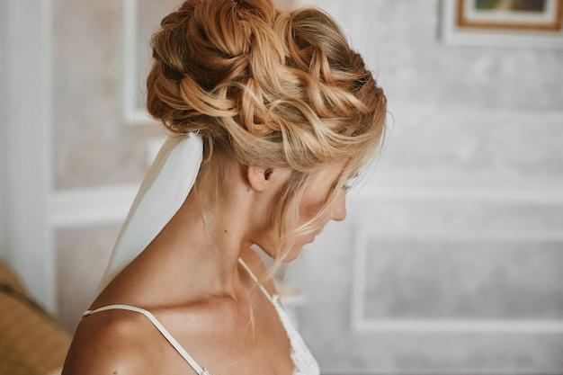 Schöne blonde junge frau mit stilvoller hochzeitsfrisur in modischen weißen spitzenwäsche, die am weinleseinnenraum aufwirft
