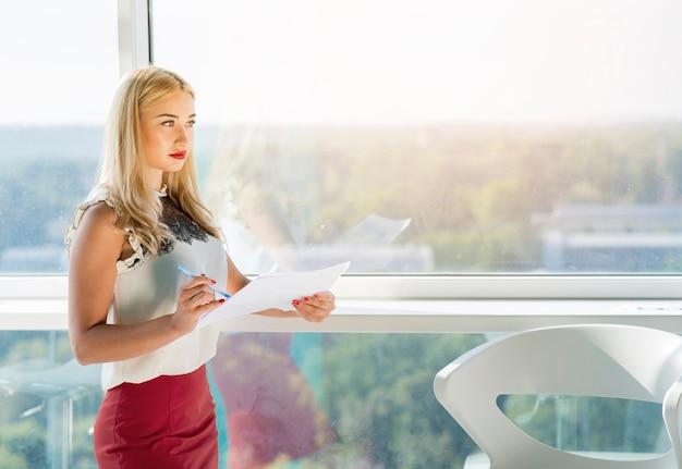Schöne blonde junge geschäftsfrau, die nahe dem fensterglas hält dokument steht