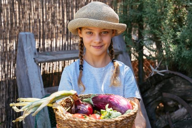 Schöne blonde kinder, die gemüsekorb halten