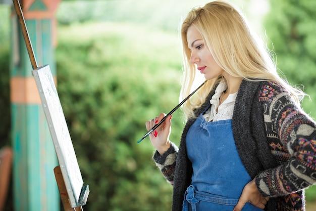 Schöne blonde künstlerin mit einem pinsel in der hand zeichnet auf leinwand in der natur.