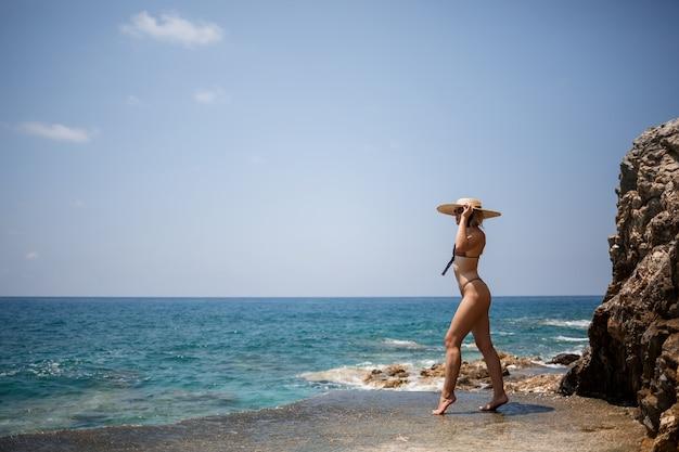 Schöne blonde mädchen im badeanzug posiert am strand auf den felsen