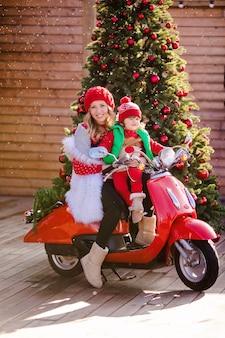 Schöne blonde mutter und sohn in weihnachtlichen roten pullovern und roten hüten sitzen auf einem roten weinlese-moped auf dem hintergrund eines weihnachtsbaumes unter dem fliegenden schnee. hochwertiges foto