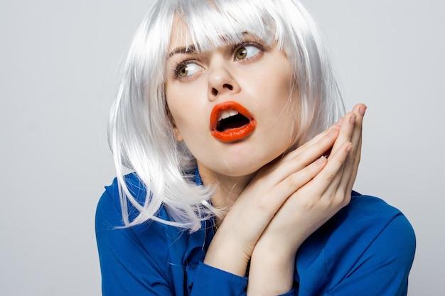 Schöne blonde rote lippen emotionen hände auf gesicht blau hemd abgeschnittene ansicht.