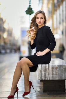 Schöne blonde russische frau im städtischen hintergrund