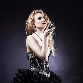Schöne blonde sängerin in einem schwarzen kleid, das ein mikrofon hält und ein lied singt