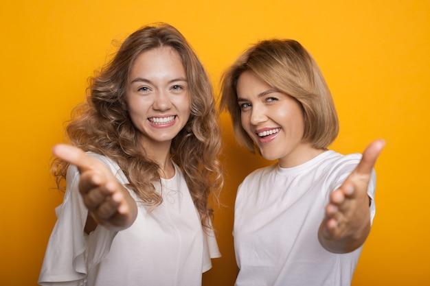 Schöne blonde schwestern, die in die kamera lächeln und mit der handfläche auf einer gelben wand zeigen