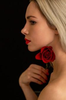 Schöne blonde stilvolle aufstellung mit einer roten rose auf einem dunklen