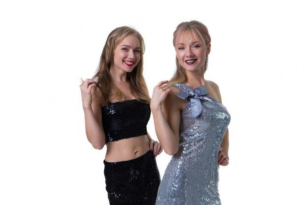 Schöne blonde zwillingsmädchen, die auf einem weiß in den glänzenden kleidern, getrennt aufwerfen