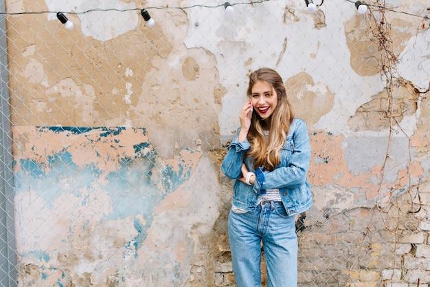 Schöne blondhaarige frau, die sinnlich vor der alten steinmauer aufwirft. junges modell, das am telefon außerhalb mit schmutzwand auf dem hintergrund spricht.