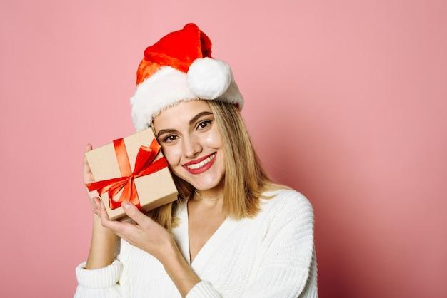 Schöne blondine auf rosa hintergrund im studio konzept für weihnachtseinkaufsgeschenk