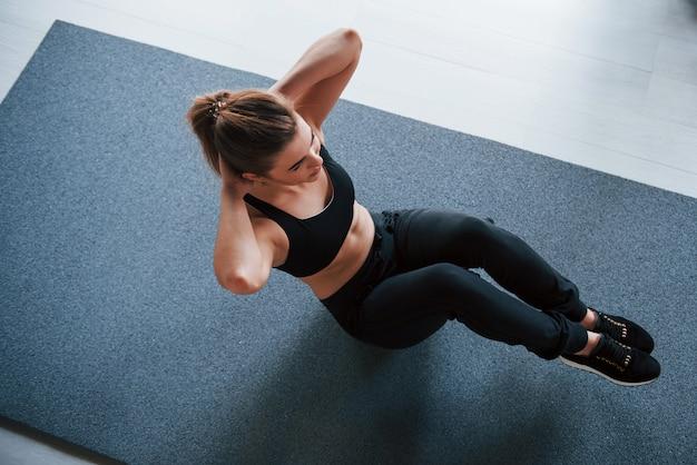 Schöne blondine. bauchmuskeln auf dem boden im fitnessstudio machen. schöne weibliche fitnessfrau