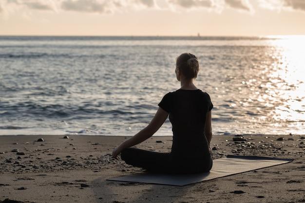 Schöne blondine der jungen frau im schwarzen, das yoga tut