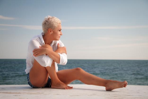 Schöne blondine der jungen frau mit einem kurzen haarschnitt kurz gesagt und einem weißen hemd, welches das meer, stehend auf der küste betrachtet