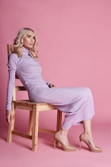 Schöne blondine der mode in gestricktem geschlossenem langem kleid, das auf einem stuhl sitzt