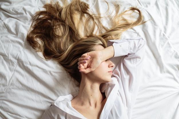 Schöne blondine des porträts, die im bett schlafen