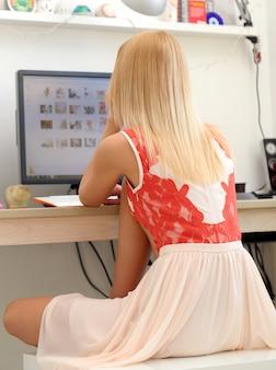 Schöne blondine, die einen computer verwendet