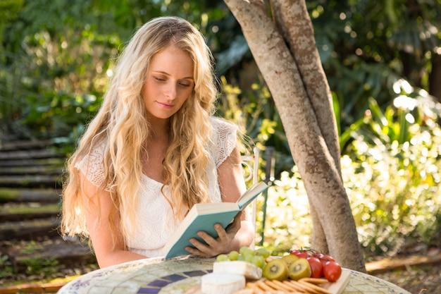 Schöne blondine, die mit lebensmittel im garten sich entspannt und liest