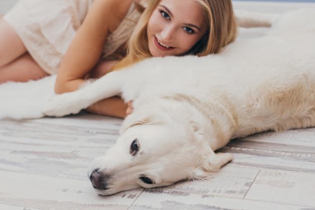 Schöne blondine, die nach hause auf boden mit dem hund liegt