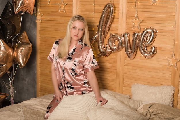 Schöne blondine im schlafanzug auf dem bett