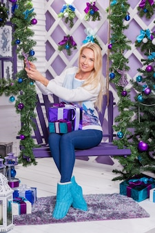 Schöne blondine in blauen hosen sitzt auf einer schaukel