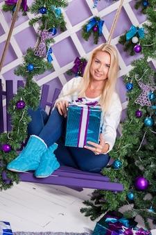 Schöne blondine in den blauen hosen, die auf einer schaukel sitzen