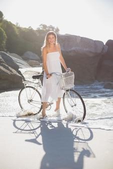 Schöne blondine in den weißen sommerkleidern, die mit fahrrad auf dem strand stehen