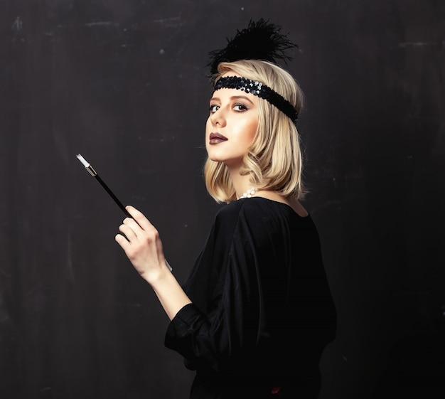 Schöne blondine in den zwanziger jahren kleiden mit pfeife auf dunklem hintergrund
