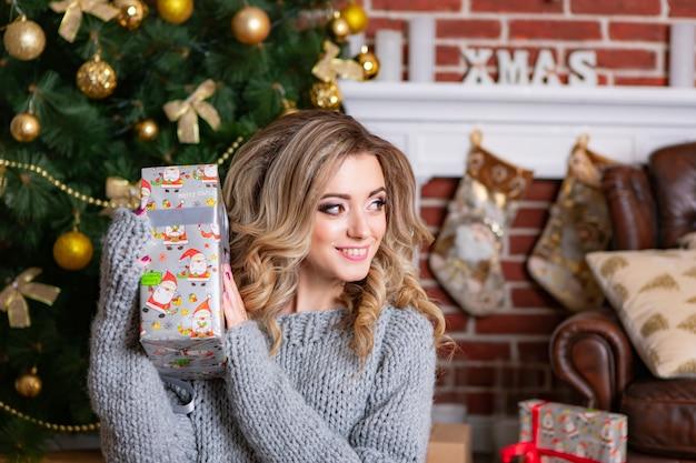 Schöne blondine in der grauen gestrickten kleidung lächelt und hält in ihren händen ein neujahrsgeschenk.
