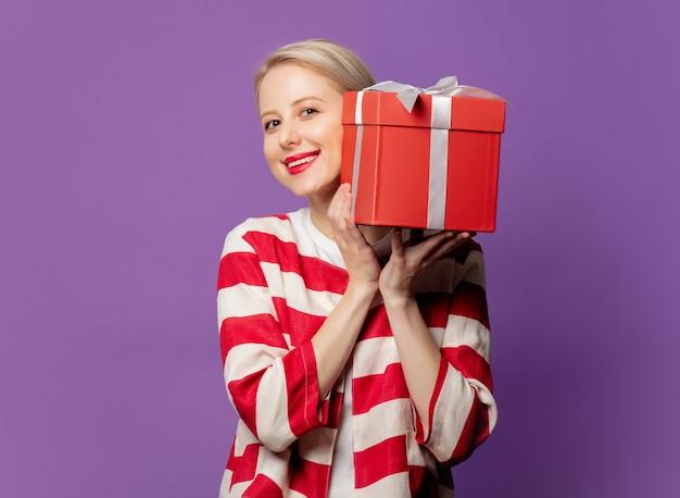 Schöne blondine in der roten jacke mit geschenkbox auf lila hintergrund