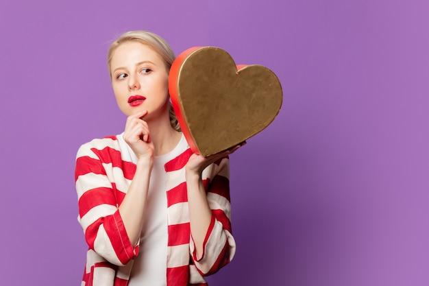 Schöne blondine in der roten jacke mit herzform-geschenkbox auf lila hintergrund