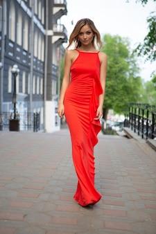 Schöne blondine in einem eleganten roten kleid und high heels