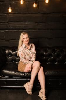 Schöne blondine in einem minirock auf einem schwarzen ledersofa