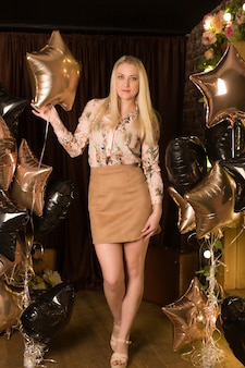 Schöne blondine in einem minirock mit luftballons
