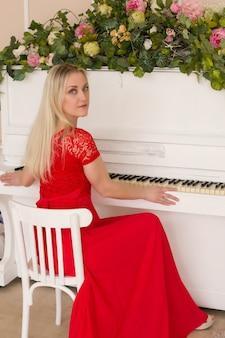 Schöne blondine in einem roten kleid am klavier