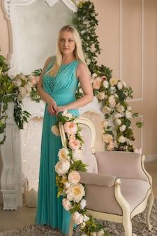 Schöne blondine in einem smaragdgrünen kleid