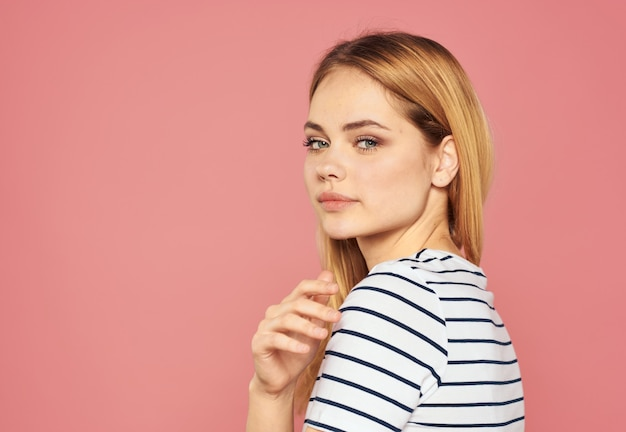 Schöne blondine in einem t-shirt auf einem rosa gestikulieren mit ihrer handmodellschnittansicht