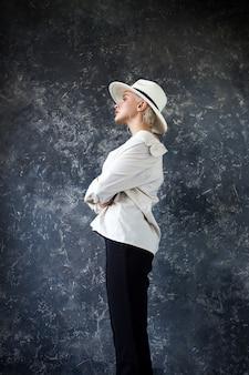 Schöne blondine in einem weißen hemd mit schwarzen hosen und einem weißen hut