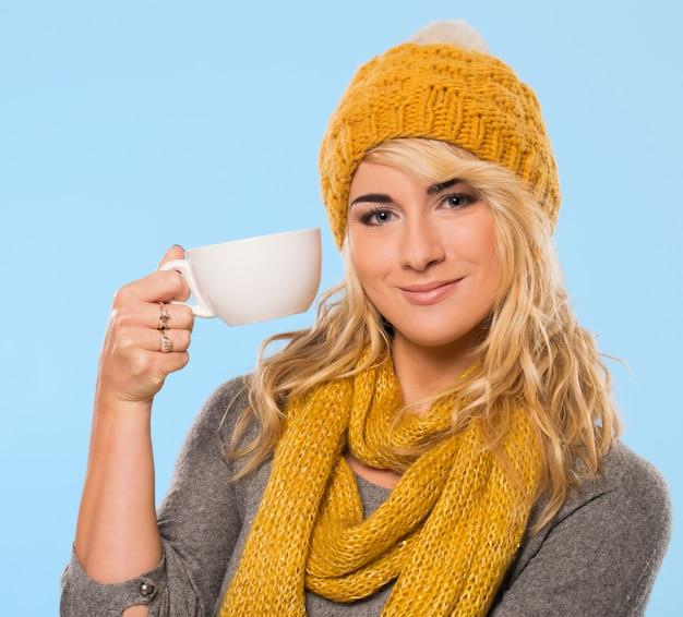 Schöne blondine in mütze und schal