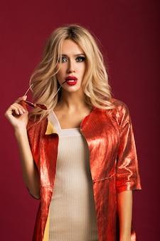 Schöne blondine in roter lederjacke