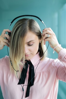 Schöne blondine in silbernen kopfhörern hört musik