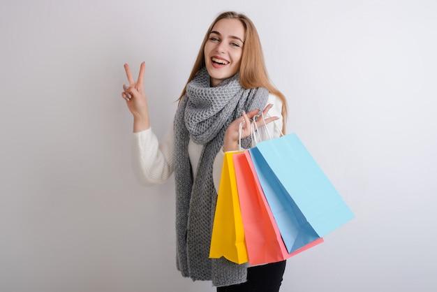 Schöne blondine in warmer kleidung hält taschen nach dem einkauf